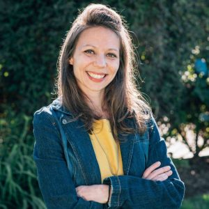 Robyn Roste, shoulder length hair wearing a jean jacket and yellow shirt and a chain with the pendant covered by her folded arms