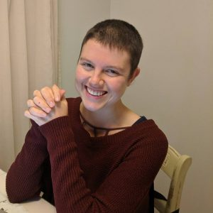 Brittany King wearing a burgandy sweater and buzz cut hair sitting at a desk with her fingers crossed together, elbows resting on the desk.