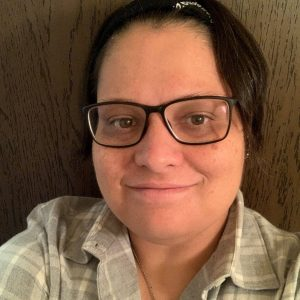Sarah Fox with mid-cut hair, black rim glasses, a white and grey flanel shirt