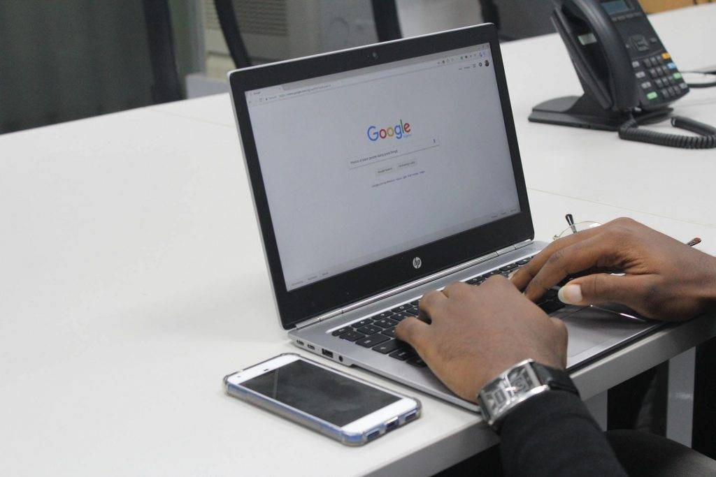 Hands typing on a laptop keyboard with a mobile phone next to the laptop