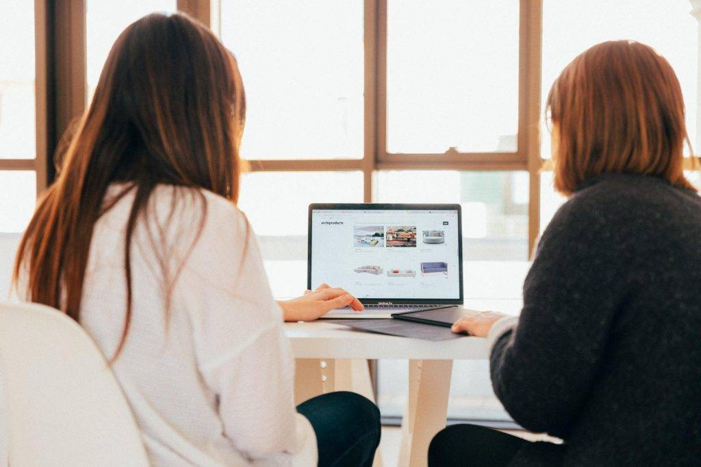Two women working together at a desk on a laptop